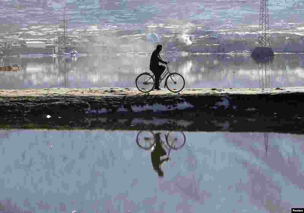 A man rides his bicycle across a lake in Kabul. (Reuters/Omar Sobhani)