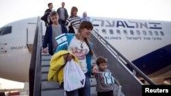 Пассажиры спускаются по трапу самолета в аэропорту в Тель-Авиве.