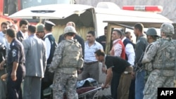 Rescue workers move a body after the suicide bombing near the Green Zone
