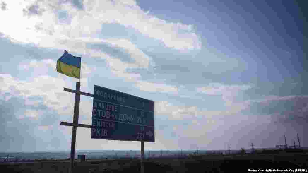 Дорога не Дебальцеве. Від цього знаку всього 15 кілометрів до міста, де в лютому 2015 року загинуло багато бійців української армії. Згодом найвище керівництво назве це успішною операцією з виведення військ. Тепер це місце, де знак, – одна із опорних точок лінії зіткнення в районі Світлодарської дуги. Сюди часто прилітають снаряди з того боку лінії зіткнення.