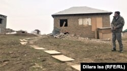 Мужчина стоит возле жилого дома на территории кооператива «Жер-Ана 1». Шымкент, 10 марта 2021 года.