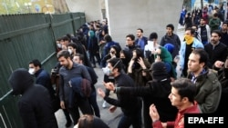 Iranian students clash with riot police during an anti-government protest around the University of Tehran on December 30.