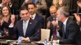 """NATO Secretary-General Jens Stoltenberg (right) looks at Macedonian Foreign Minister Nikola Dimitrov as he holds a pen aloft during the signing of an """"accession protocol"""" in a ceremony at NATO headquarters in Brussels on February 6."""