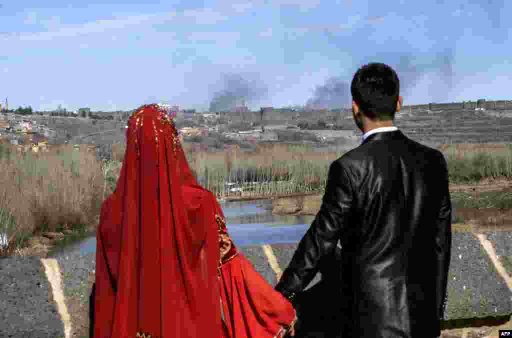 A couple holds hands for a wedding photo as they look at smoke rising over the district of Sur in Diyarbakir, Turkey, after clashes between Kurdish rebels and Turkish forces. (AFP/Ilyas Akengin)