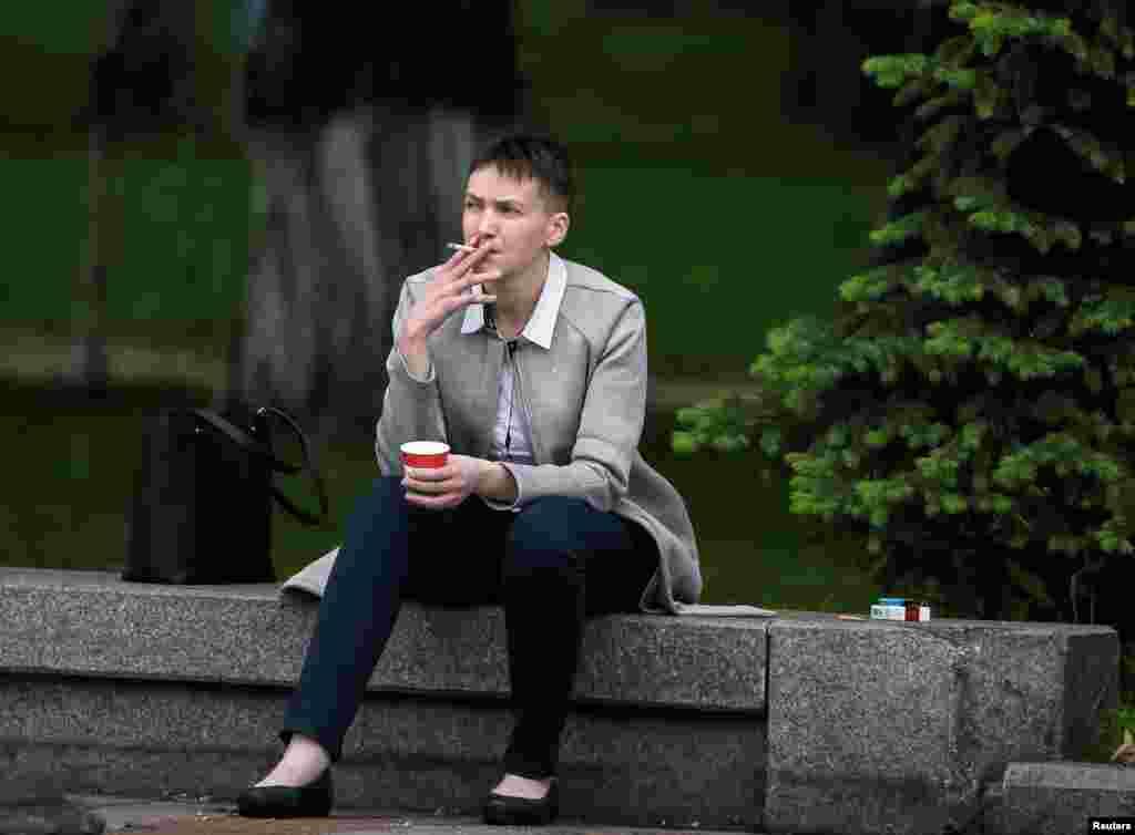 უკრაინელი სამხედრო მფრინავი და პარლამენტის დეპუტატი ნადია სავჩენკო სიგარეტს ეწევა და ყავას სვამს პარლამენტის შენობის წინ, პარლამენტის პირველი სხდომის წინ, რომელსაც იგი დაესწრო რუსეთში პატიმრობიდან გათავისუფლების შემდეგ. (ფოტო: Reuters)