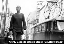 Молодая женщина в задумчивости идет по центру Праги