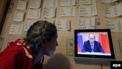 A woman watches a news program showing Russian President Vladimir Putin making a statement about the Syria situation in St. Petersburg on September 30.