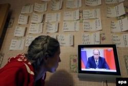Женщина смотрит выпуск телевизионных новостей, где показывают речь президента России Владимира Путина на заседании правительства. Санкт-Петербург, 30 сентября 2015 года.