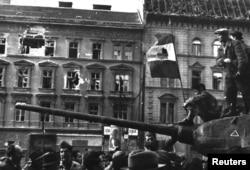 Бійці сидять на вершині танку з революційним прапором у Будапешті під час повстання проти радянського угорського комуністичного режиму в 1956 році