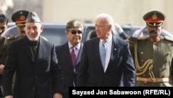 U.S. Vice President Joe Biden (center) and Afghan President Hamid Karzai (left) inspect an honor guard during their meeting in Kabul.