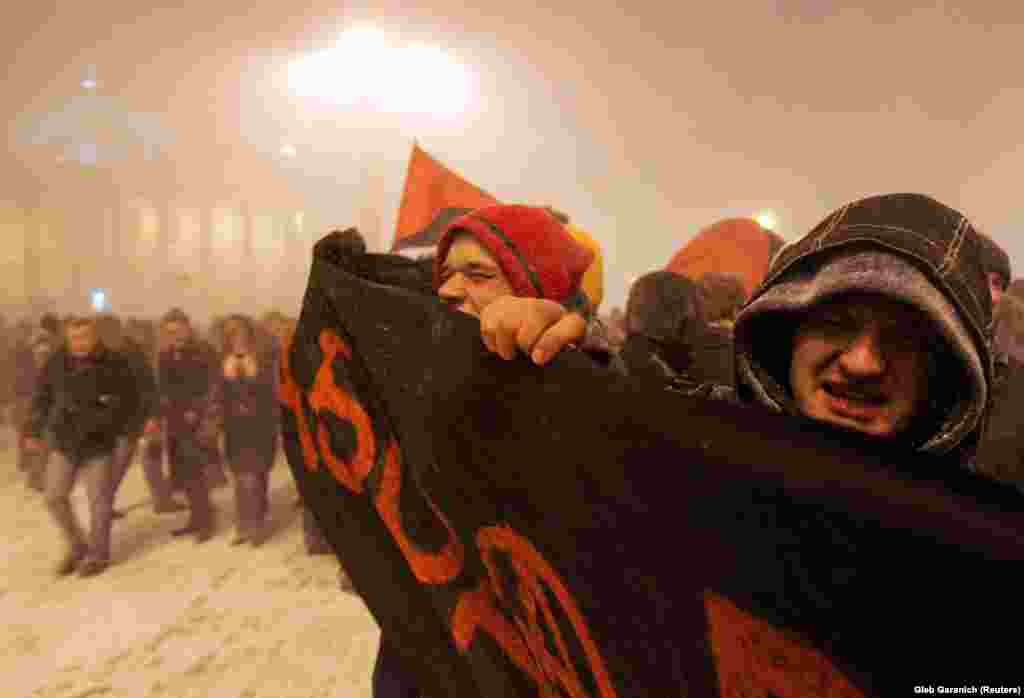 Antigovernment protesters push through a driving blizzard in Minsk.