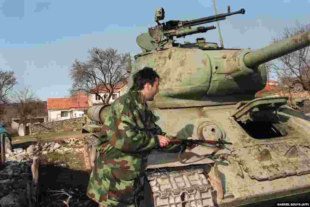 An ethnic Serbian fighter next to a Soviet-made T-34/76A medium tank built during World War II, in Knin, Croatia, on February 3, 1993.