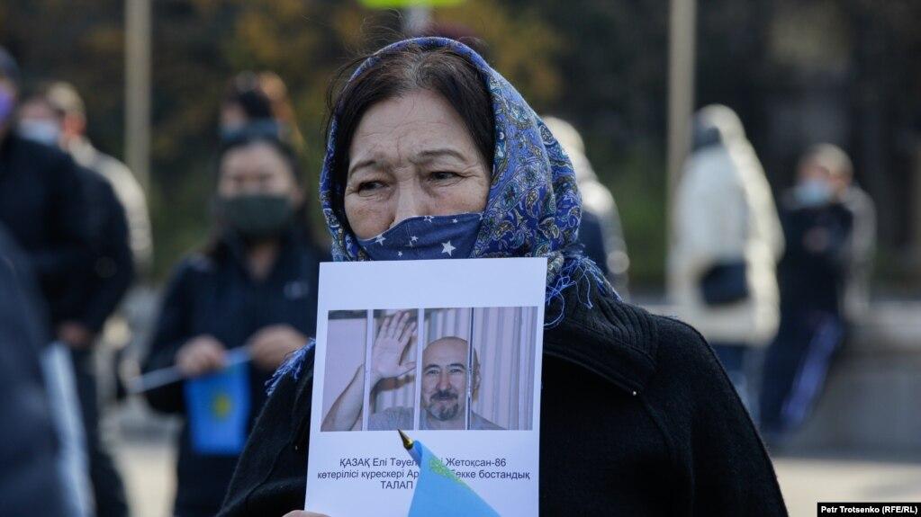 Женщина держит плакат с требованием освободить политзаключенного Арона Атабека на митинге Алматы. 31 октября 2020 года.