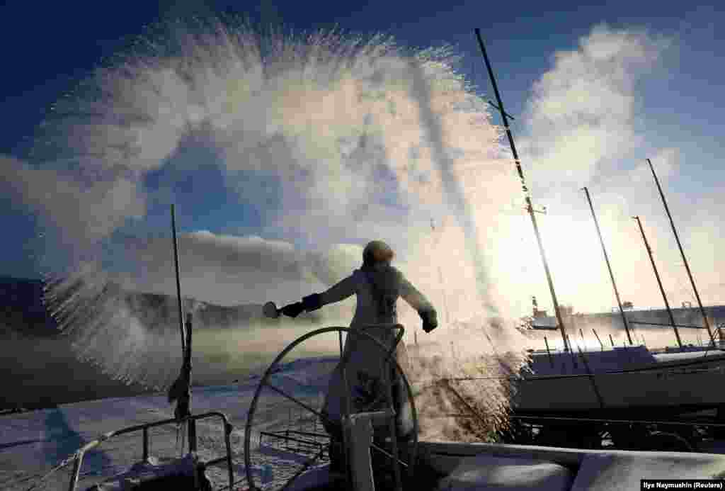 A member of the Skipper yacht club dressed as Snegurochka (Snowmaiden) slops over hot water during an event dedicated to the end of the sailboat season, with the air temperature at about minus 33 degrees Celsius outside the Siberian city of Krasnoyarsk on December 5. (Reuters/Ilya Naymushin)