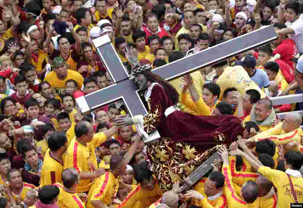 Devotees carry the statue of the Black Nazarene during the start of an annual procession in Manila. The Black Nazarene is a life-size wooden statue of Jesus Christ carved in Mexico and brought to the Philippines in the 17th century. It is believed to have healing powers in the predominantly Roman Catholic country. It is paraded through the narrow streets of Manila's old city from dawn to midnight. (Reuters/Erik De Castro)