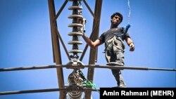 کارگری در قزوین در حال تعمیر یک دکل برق است