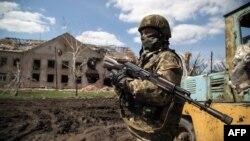 Ілюстраційне фото. Український військовослужбовець стоїть біля зруйнованої будівлі в селі Піски, 23 квітня 2015 року