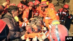 Turkey -- Rescuers carry a survivor from a collapsed building after an earthquake in Van, 09Nov2011