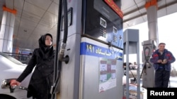 An Iranian woman fuels her car at a gas station in Tehran, January 25, 2016