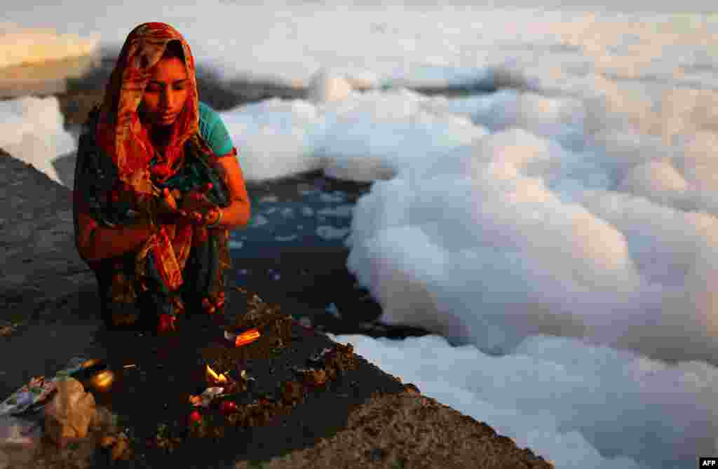 An Indian Hindu devotee prays near the polluted Yamuna River in New Delhi. India's Supreme Court said that all measurements of water quality indicate that it is highly polluted and urged authorities to tackle the problem. More than 2,400 million liters of untreated sewage flows into the Yamuna every day. (AFP/Andrew Caballero-Reynolds)