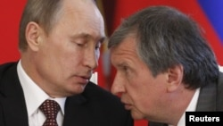 Ivan Sechin's father, Igor (right), is a longtime confidant of Russian President Vladimir Putin
