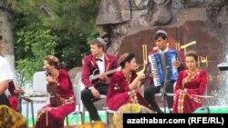 Ýaş aýdymçylar Magtymgulynyň heýkeliniň öňünde konsert berýärler. Aşgabat, Maý, 2012 ý.