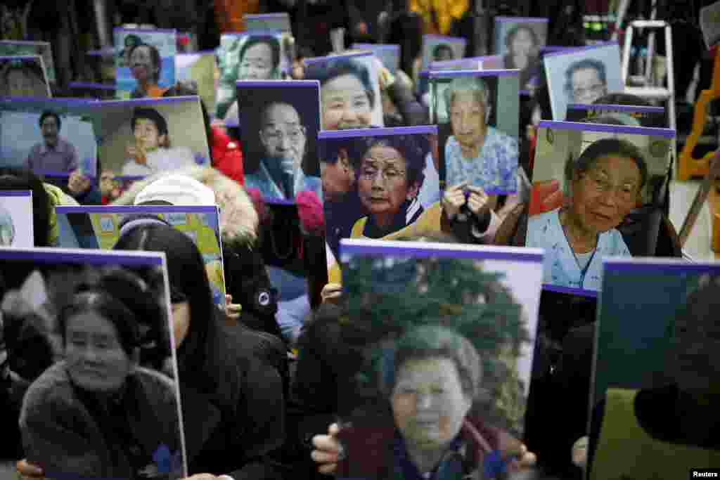 "Students hold portraits of deceased former South Korean ""comfort women,"" who were forced into sexual slavery by the Japanese Army in World War II, during a weekly anti-Japan rally in front of Tokyo's embassy in Seoul on December 30. (Reuters/Kim Hong-Ji)"