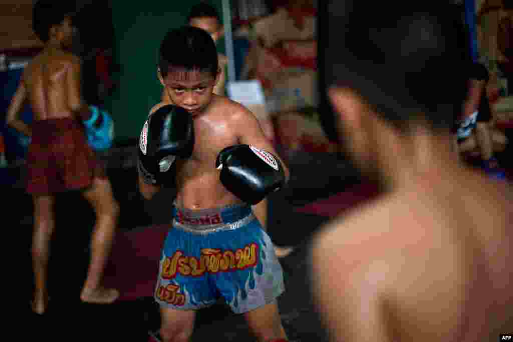 Young Muay Thai boxer resting and getting coached between rounds.