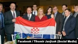 Kolinda Grabar Kitarović u društvu delegacije koja drži zastavu sa ustaškim grbom