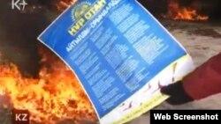 """Мұнайшы киімін киген азамат президентшіл """"Нұр Отан"""" партиясының жарнамасын өртеп жатыр. Жаңаөзен, 16 желтоқсан, 2011 жыл."""