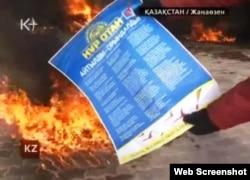 """Жумушчу кийиминдеги адам президентчил """"Нур Отан"""" партиясынын плакатын отко салууда. Жаңы-Өзөн, 16-декабрь."""