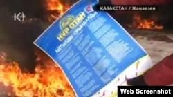 """Человек в рабочей спецовке бросает в огонь предвыборный плакат президентской партии «Нур Отан». Жанаозен, 16 декабря 2011 года. Скриншот с видеосюжета телеканала """"К-плюс""""."""