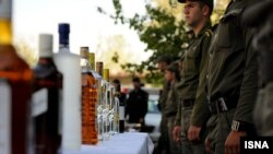 Iranian police display alcohol after breaking up illicit parties and making arrests in Tehran in October 2010
