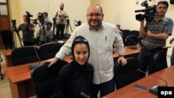 Iranian-American correspondent Jason Rezaian and his Iranian wife, Yeganeh Salehi, pose while covering a press conference at Iran's Foreign Ministry in Tehran in September 2013.