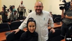 Iranian-American Washington Post correspondent Jason Rezaian (standing) and his Iranian wife Yeganeh Salehi pose while covering a press conference at Iran's Foreign Ministry in Tehran in September 2013.