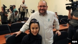 Iranian-American Washington Post correspondent Jason Rezaian (top) and his Iranian wife, Yeganeh Salehi, pose while covering a press conference at Iran's Foreign Ministry in Tehran in September 2013.