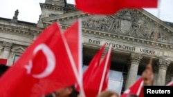 Germany - Demonstrators wave Turkish flags in front of the Reichstag, the seat of the lower house of parliament Bundestag in Berlin, Germany, June 1, 2016
