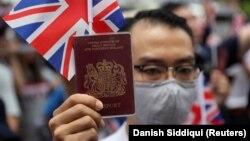 Ҳонконгдаги акцияда Британия паспортини кўтариб турган намойишчи, 2019 йил сентябри.