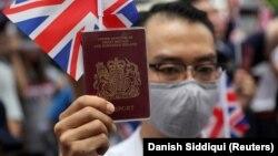 Улуу Британиянын Гонконгдогу консулдугунун алдына чогулган митингчилердин бири британ паспортун көтөрүп турат, 1-сентябрь 2019-жыл.