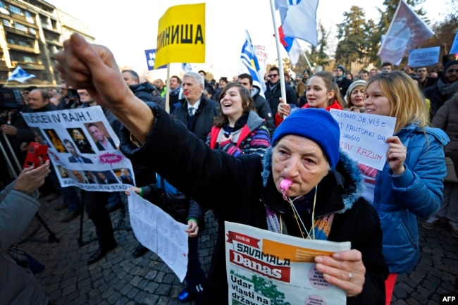 An elderly woman blows a whistle as protesters march during an antigovernment protest in Belgrade on February 15.