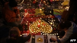 People light candles at a makeshift memorial at Brussels' Place de la Bourse.