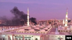 The Prophet Mohammed Mosque with smoke rising in the background in the holy city of Medina on July 4.