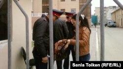 Полицейские проверяют содержимое сумочки женщины, проходящей на территорию Атырауского областного суда.