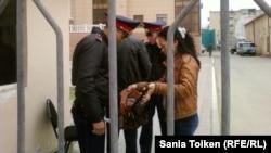 Атырау облыстық сотының алдында азаматтарды тексеріп жатқан полицейлер. (Көрнекі сурет)