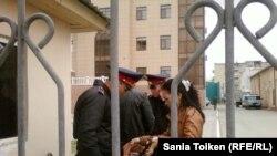 Полицейские проверяют содержимое сумочки женщины, проходящей на территорию Атырауского областного суда. Иллюстративное фото.