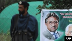 Pakistan -- A policeman stands guard next to a banner showing an image of former military ruler Pervez Musharraf near his residence in Islamabad, November 6, 2013