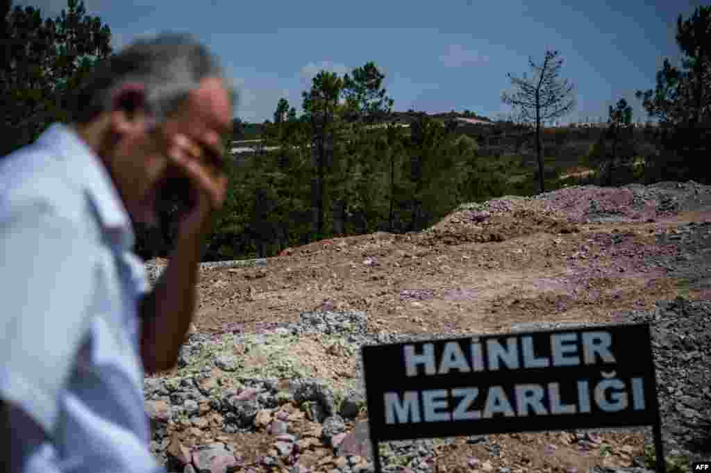"A man stands next to a sign reading ""Traitors' Cemetery"" in Turkish at the site where unmarked graves were built especially by the Istanbul municipality for those who died attempting a failed coup on July 15."