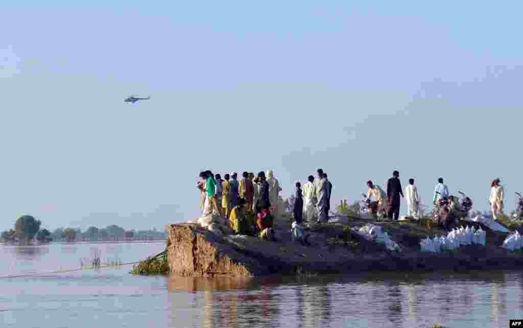 Pakistani villagers gather on higher ground as floodwaters enter the Hafizabad district of Punjab Province.