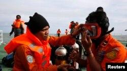 Индонезийские дайверы, занятые в поисковой операции по обнаружению тел пассажиров лайнера AirAsia. 2 января 2015 года.