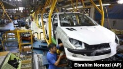 In this Oct. 11, 2014 file photo an Iranian worker assembles a Peugeot 206 at the state-run Iran-Khodro automobile manufacturing plant near Tehran, Iran.
